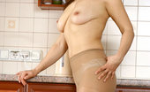 Anilos Lana Sultry housewife Lana slips off her dress and rubs cream on her big boobs in the kitchen