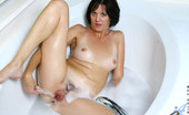 Anilos Katie Alluring cougar Katie fucks her sweet pink pussy with a clear glass dildo in the bathtub