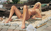 Gina Lynn Blonde babe Gina Lynn strips before oiling up and posing for the camera on the cobblestone