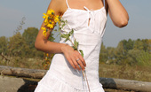 Amour Angels Alina ROMANTIC STORY Attractive gal plays with her neat white dress while posing outdoors.