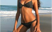 Polliana Polliana Looking Like A Swimsuit Model Posing On The Beach In A Black Bikini With White Polka Dots.