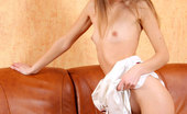 Nubiles Emanuelle 245261 Slender Brunette With Nice Long Legs Spreading Wide On The Couch