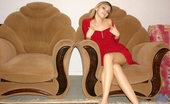 Nubiles Katrina Alluring Katrina In Red Dress Seductively Sitting On Chair