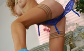 Lacy Nylons Emilia Kinky Babe Attaching Her White Slight Sheen Stockings To Her Blue Garter Lacy Nylons